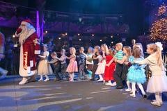 Santa Claus leidt de kinderen een vrolijke vakantiedansen De Kerstman draagt giften Santa Claus op stadium Stock Afbeeldingen