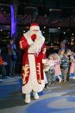Santa Claus leidt de kinderen een vrolijke vakantiedansen De Kerstman draagt giften Santa Claus op stadium Stock Afbeelding