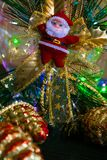 Santa Claus leksak på bokehbakgrund och suddig ljusförgrund, lyktafackla som tänder vägen Nytt års baner, affisch, fotografering för bildbyråer