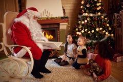 Santa Claus-Lesemärchen mit Kindern lizenzfreie stockbilder
