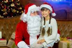 Santa Claus and lettle girl with Christmas gifts Royalty Free Stock Images