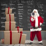 Santa Claus and list of gifts delivery. Santa Claus with megaphone with list of gifts delivery in a blackboard Stock Images