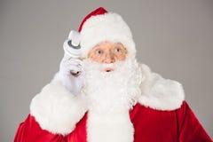 Santa Claus listening music with headphones. Happy Santa Claus listening music with headphones and posing Royalty Free Stock Photos