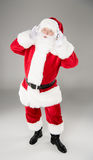 Santa Claus listening music with headphones. Happy Santa Claus listening music with headphones and posing Royalty Free Stock Photo