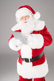 Santa Claus listening music with headphones. Happy Santa Claus listening music with headphones and using digital tablet Stock Photography