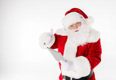 Santa Claus listening music with headphones. Happy Santa Claus listening music with headphones and using digital tablet Royalty Free Stock Photography