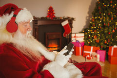 Santa claus listening music with his smartphone Royalty Free Stock Image