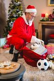 Santa claus listening music on mobile phone at home royalty free stock photo