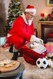 Santa claus listening music on mobile phone at home. During christmas time Stock Images