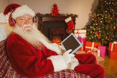 Santa claus listening music and using tablet. At home in the living room Royalty Free Stock Photo