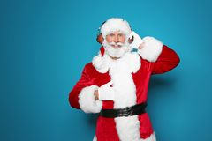 Santa Claus listening to Christmas music. On color background royalty free stock photo