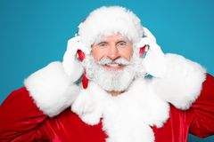 Santa Claus listening to Christmas music. On color background stock photo
