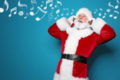 Santa Claus listening to Christmas music. On color background stock photos