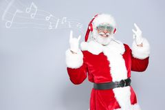 Santa Claus listening to Christmas music. On color background royalty free stock images