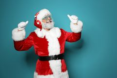 Santa Claus listening to Christmas music. On color background royalty free stock photos