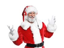 Santa Claus listening to Christmas music. On white background stock photography