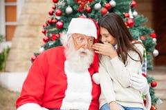 Santa Claus Listening To Girl's Wish. Shocked Santa Claus listening to girl's wish in front of Christmas tree Royalty Free Stock Photography