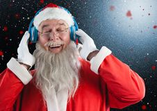 Santa claus listening to music on headphones. Against digitally generated background Royalty Free Stock Image