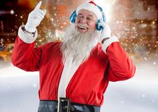Santa claus listening to music on headphones. Against digitally generated background Stock Photos