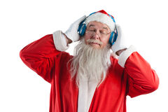 Santa claus listening to music on headphones. Against white background Royalty Free Stock Photo