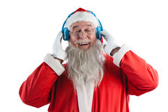 Santa claus listening to music on headphones. Happy santa claus listening to music on headphones against white background Stock Photos