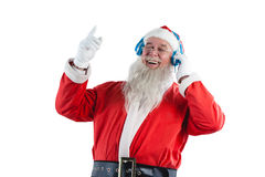 Santa claus listening to music on headphones. Happy santa claus listening to music on headphones against white background Royalty Free Stock Photos