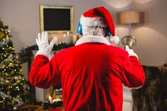Santa claus listening to music on headphones at home during christmas time. Rear view of santa claus listening to music on headphones at home during christmas Royalty Free Stock Photos
