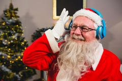 Santa claus listening to music on headphones at home. Smiling santa claus listening to music on headphones at home Royalty Free Stock Image