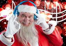 Santa claus listening to music headphones. Portrait of santa claus listening to music on headphones against digitally generated christmas background Stock Photo