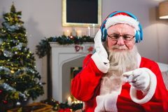 Santa Claus listening to music on headphones. Portrait of santa claus listening to music on headphones at home during christmas time Stock Photo