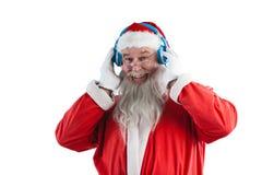 Santa claus listening to music on headphones. Portrait of smiling santa claus listening to music on headphones against white background Stock Photos