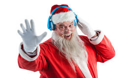 Santa claus listening to music on headphones. Portrait of smiling santa claus listening to music on headphones against white background Royalty Free Stock Images