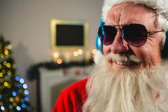 Santa Claus listening to music on headphones. At home Stock Images