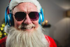 Santa Claus listening to music on headphones. At home Stock Photography
