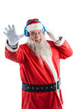 Santa claus listening to music on headphones. Smiling santa claus listening to music on headphones against white background Stock Photography
