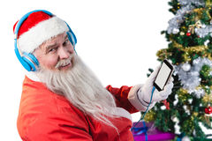 Santa claus listening to music on mobile phones. Against white background Royalty Free Stock Photography