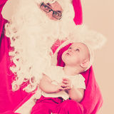 Santa claus with little baby. Stock Image