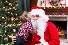 Santa Claus and little child boy. Kid telling his Stock Images
