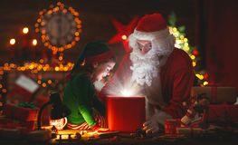 Santa Claus and little elf with magic gift for Christmas Royalty Free Stock Images