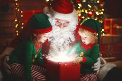 Santa Claus and little elves with magic gift for Christmas
