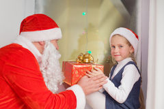 Santa Claus with a little girl in Christmas. Santa Claus on a visit at little girl wishes Merry Christmas Stock Images