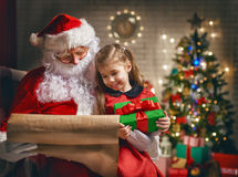 Santa Claus and little girl. Santa Claus giving a present to a little cute girl Stock Photography