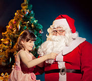 Santa Claus  and little girl holding gift Stock Photo