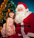 Santa Claus and little girl holding gift Royalty Free Stock Image