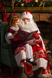 Santa Claus and little girl reading book. Against Christmas tree and fireplace Royalty Free Stock Photography