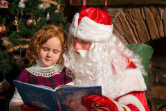 Santa Claus and little girl reading book Stock Photography
