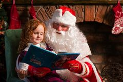 Santa Claus and little girl reading book. Against Christmas tree and fireplace Royalty Free Stock Photos
