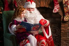 Santa Claus and little girl reading book. Against Christmas tree and fireplace Royalty Free Stock Image