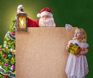 Santa Claus with a little girl, vintage lantern and a poster Royalty Free Stock Image