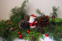 Santa Claus. Little Santa Claus surrounded by fir branches and fir cones Royalty Free Stock Photo